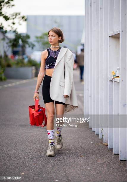 A guest wearing cropped sports top biker pants is seen outside MUF10 during the Copenhagen Fashion Week Spring/Summer 2019 on August 8 2018 in...