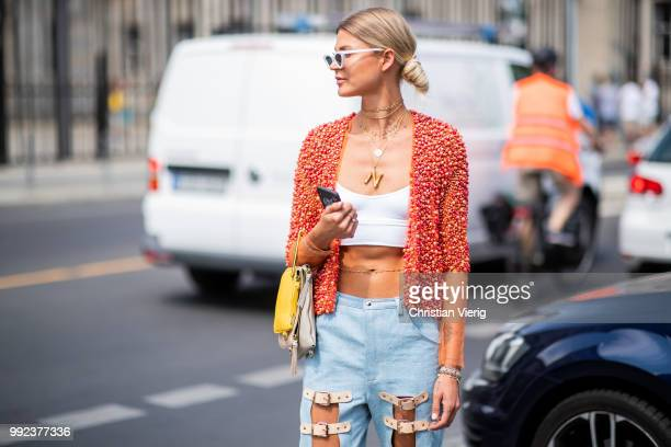 A guest wearing cropped top ripped denim jeans Balenciaga sneakers seen outside Marina Hoermanseder during the Berlin Fashion Week July 2018 on July...