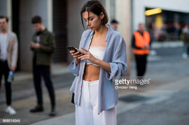 Guest wearing cropped top, white pants, button shirt during Mercedes-Benz Fashion Week Resort 19 Collections at Carriageworks on May 17, 2018 in...