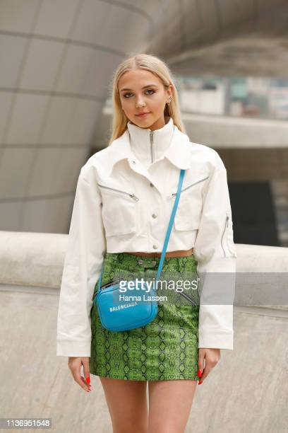 Guest wearing cropped white jacket, green snake leather skirt and Balenciaga bag is seen at the Hera Seoul Fashion Week 2019 F/W at Dongdaemun Design...