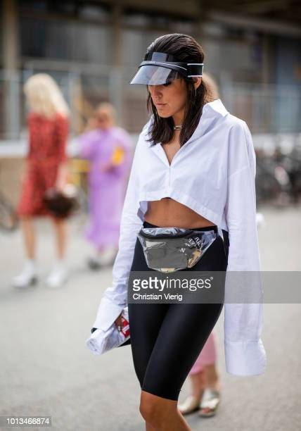 A guest wearing cycle pants belt bag cropped top boots is seen outside JLindeberg during the Copenhagen Fashion Week Spring/Summer 2019 on August 8...