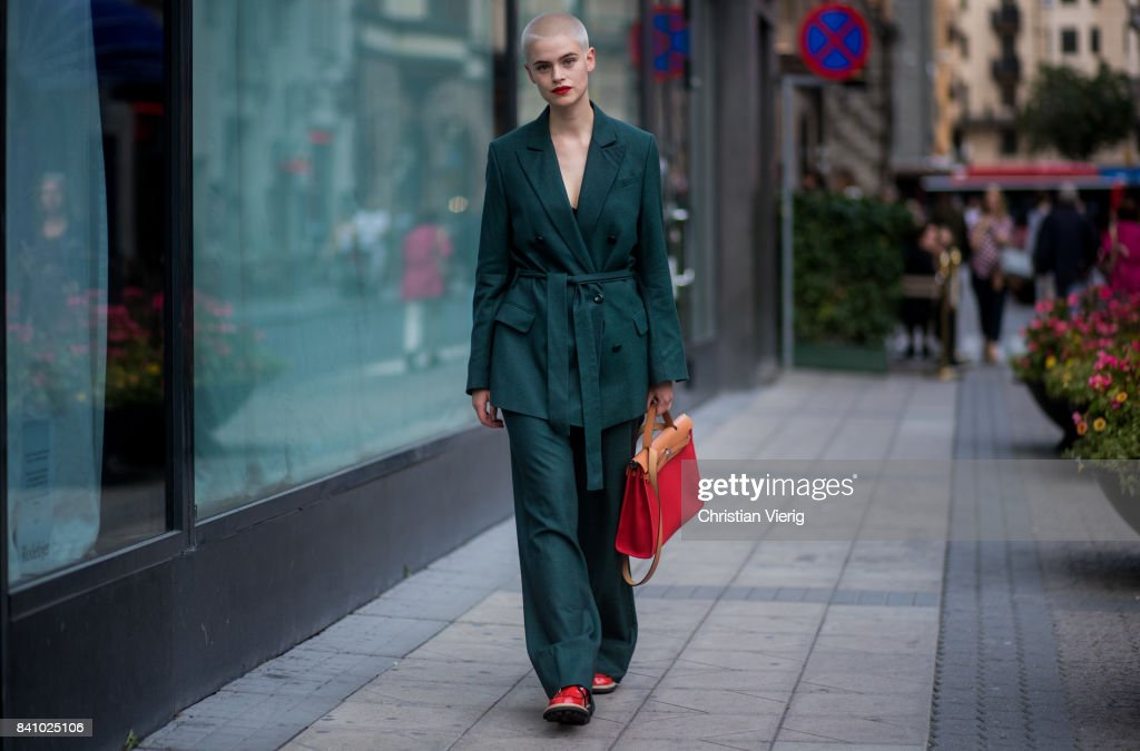 A guest wearing dark green jacket and pants, red bag outside Rodebjer on August 30, 2017 in Stockholm, Sweden.