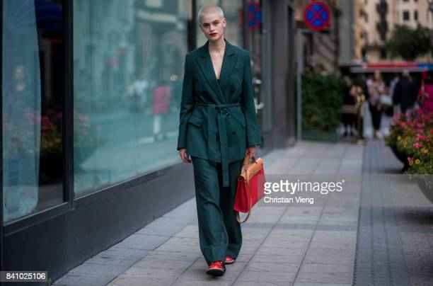 A guest wearing dark green jacket and pants red bag outside Rodebjer on August 30 2017 in Stockholm Sweden