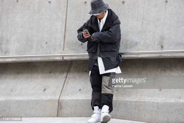 Guest wearing denim bucket hat black denim jacket and white sneakers is seen at the Hera Seoul Fashion Week 2019 F/W at Dongdaemun Design Plaza at...