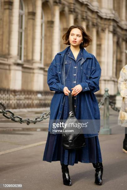 Guest wearing denim dress, denim matching shirt jacket, black leather Prada bag and black pointy boots outside Vivienne Westwood show during Paris...