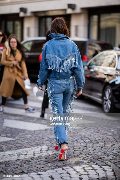A guest wearing denim jacket and jeans with fringes is seen during Paris Fashion Week Womenswear Spring/Summer 2019 on September 29 2018 in Paris...