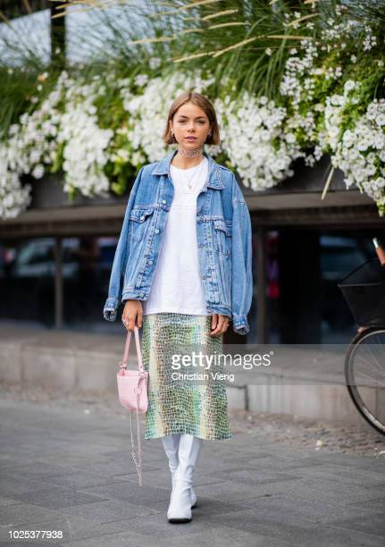A guest wearing denim jacket midi skirt white boots pink bag during Stockholm Runway SS19 on August 30 2018 in Stockholm Sweden