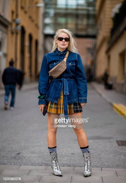 A guest wearing denim jacket mini skirt fanny bag during Stockholm Runway SS19 on August 30 2018 in Stockholm Sweden