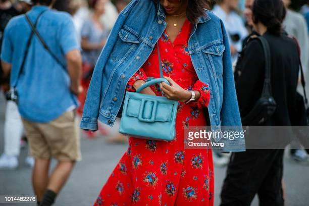 A guest wearing denim jacket red dress blue bag is seen outside Saks Potts during the Copenhagen Fashion Week Spring/Summer 2019 on August 9 2018 in...