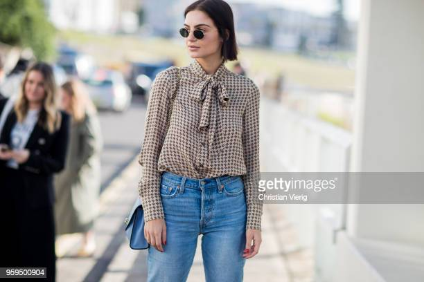 A guest wearing denim jeans blue bag blouse during MercedesBenz Fashion Week Resort 19 Collections at Icebergs Dining Room on May 17 2018 in Sydney...