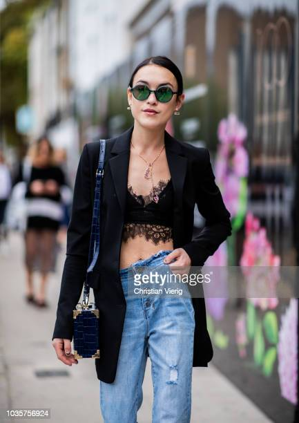 A guest wearing denim jeans cropped top black jacket is seen outside Natasha Zinko during London Fashion Week September 2018 on September 18 2018 in...