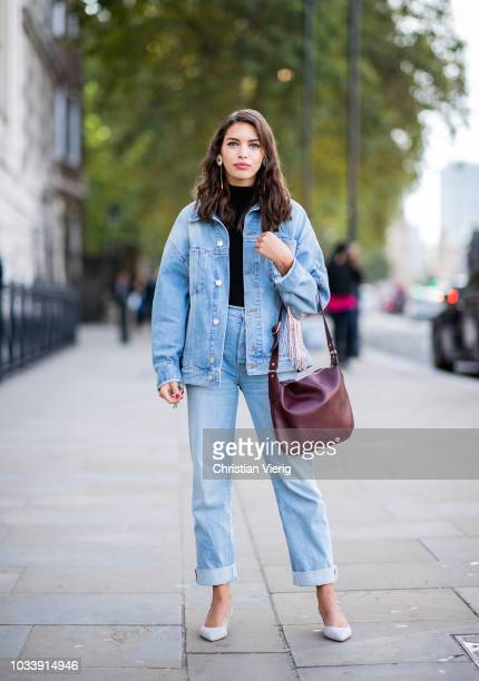 A guest wearing denim jeans denim jacket earring is seen outside Anya Hindmarch during London Fashion Week September 2018 on September 15 2018 in...