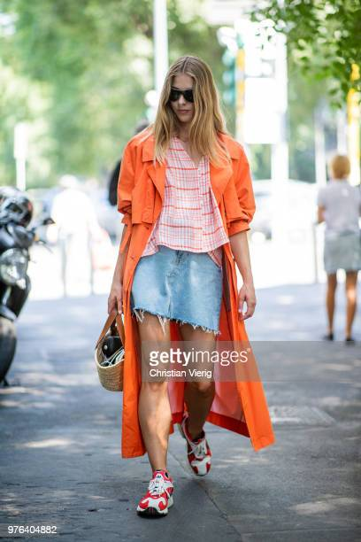 A guest wearing denim mini skirt orange trench coat Loewe bag is seen outside M1992 during Milan Men's Fashion Week Spring/Summer 2019 on June 16...