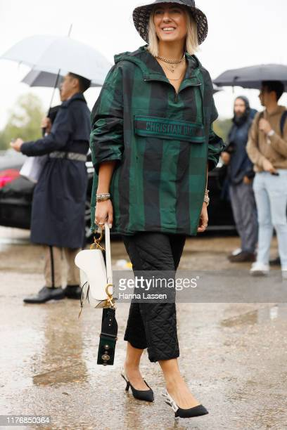 A guest wearing Dior bucket hat jumper white bag and shoes outside Dior on September 24 2019 in Paris France