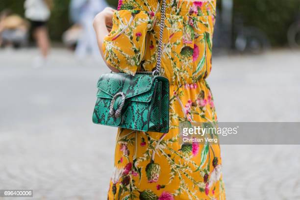 A guest wearing dress with floral print and green Gucci bag is seen during Pitti Immagine Uomo 92 at Fortezza Da Basso on June 15 2017 in Florence...