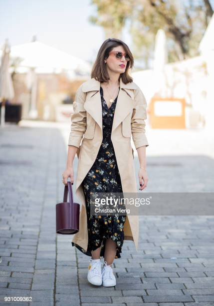 Guest wearing dress with floral print and trench coat is seen during Tel Aviv Fashion Week on March 12, 2018 in Tel Aviv, Israel.