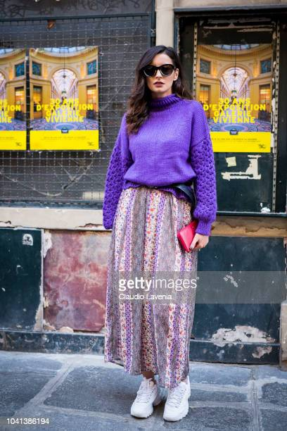 A guest wearing e purple sweater printed long skirt and white sneakers is seen before the Mugler show on September 26 2018 in Paris France