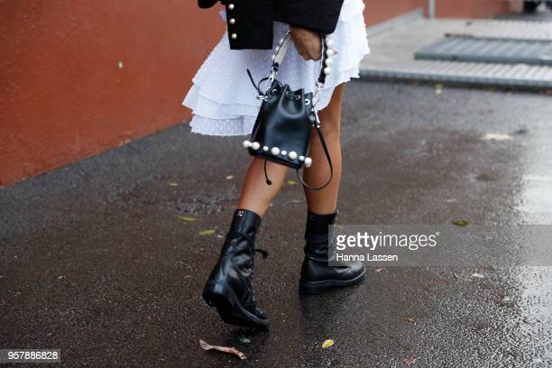 A guest wearing Fendi clutch and Chanel boots during MercedesBenz Fashion Week Resort 19 Collections at Royal Hall of Industries on May 13 2018 in...
