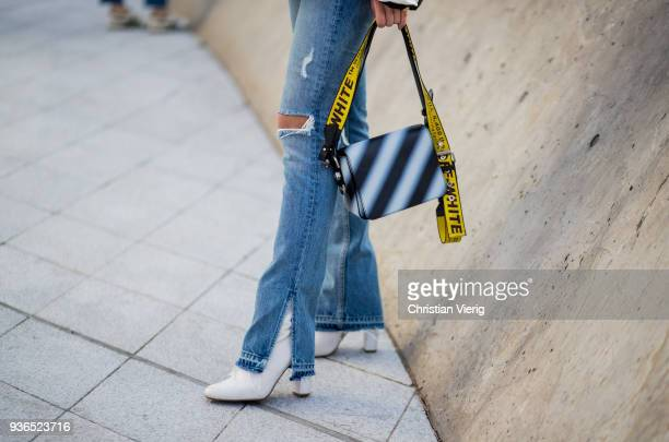 A guest wearing flared denim jeans with slit Off White bag is seen at the Hera Seoul Fashion Week 2018 F/W at Dongdaemun Design Plaza on March 22...