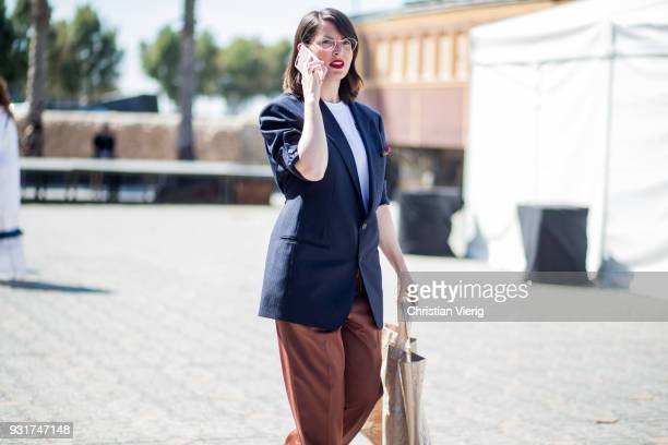 A guest wearing flared pants Comme des Garcons bag is seen during Tel Aviv Fashion Week on March 13 2018 in Tel Aviv Israel