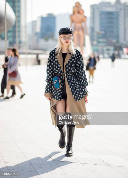 A guest wearing flat cap belted trench and belted jacket with print is seen at the Hera Seoul Fashion Week 2018 F/W at Dongdaemun Design Plaza on...
