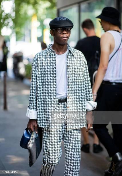 Guest wearing flat cap, black white suit is seen outside M1992 during Milan Men's Fashion Week Spring/Summer 2019 on June 16, 2018 in Milan, Italy.