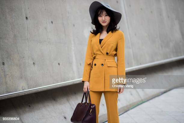 Guest wearing floppy hat, mustard suit, YSL bag is seen at the Hera Seoul Fashion Week 2018 F/W at Dongdaemun Design Plaza on March 20, 2018 in...