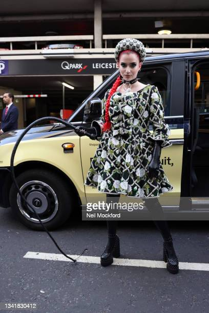 Guest wearing floral printed dress, black boots, whip attends Richard Quinn at The Londoner Hotel during London Fashion Week September 2021 on...