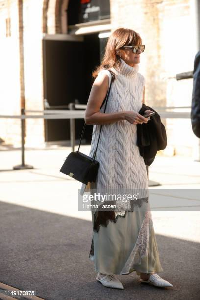 A guest wearing Givenchy sunglasses white knit top and silk skirt with white mules at MercedesBenz Fashion Week Resort 20 Collections on May 15 2019...