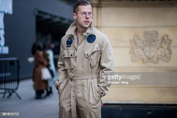 A guest wearing glasses beige overall during London Fashion Week Men's January 2018 on January 6 2018 in London England