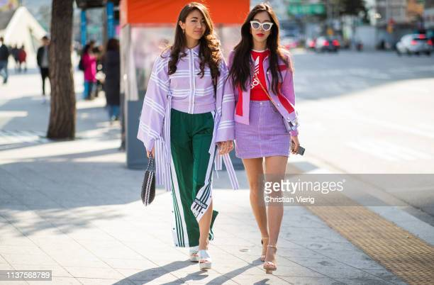 A guest wearing green Adidas pants pink top with wide sleeves and a guest wearing mini skirt jacket seen at the Hera Seoul Fashion Week 2019 F/W at...