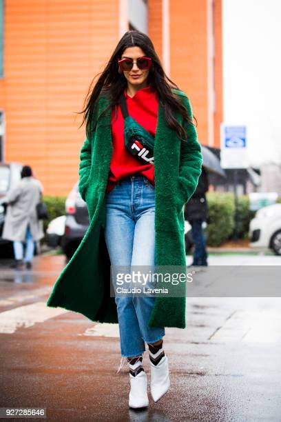 A guest wearing green coat Fila bag and Aperlai white heels boots is seen in the streets of Paris before the Balenciaga show during Paris Fashion...