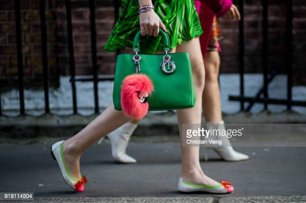 A guest wearing green Dior bag Fendi accessory flat shoes outside Mulberry during London Fashion Week February 2018 on February 16 2018 in London...