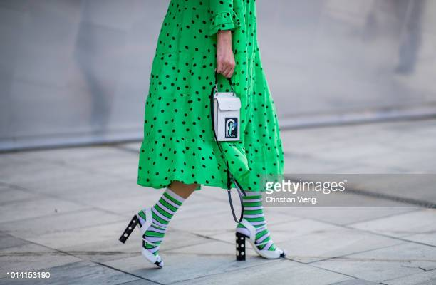 A guest wearing green dress white heels green socks bag is seen outside Designers Remix during the Copenhagen Fashion Week Spring/Summer 2019 on...