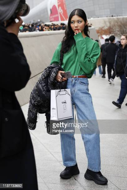 Guest wearing green jumper and jeans is seen at the Hera Seoul Fashion Week 2019 F/W at Dongdaemun Design Plaza at Dongdaemun Design Plaza on March...