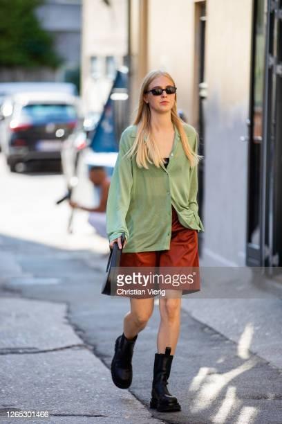 Guest wearing green shirt, brown shorts, black boots is seen outside Samsøe & Samsøe during Copenhagen Fashion Week Spring/Summer 2021 on August 11,...