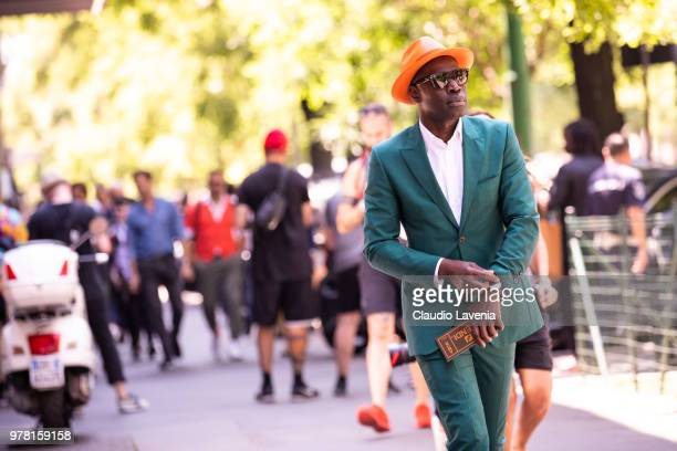 A guest wearing green suit and orange hat is seen in the streets of Milan after the Fendi show during Milan Men's Fashion Week Spring/Summer 2019 on...