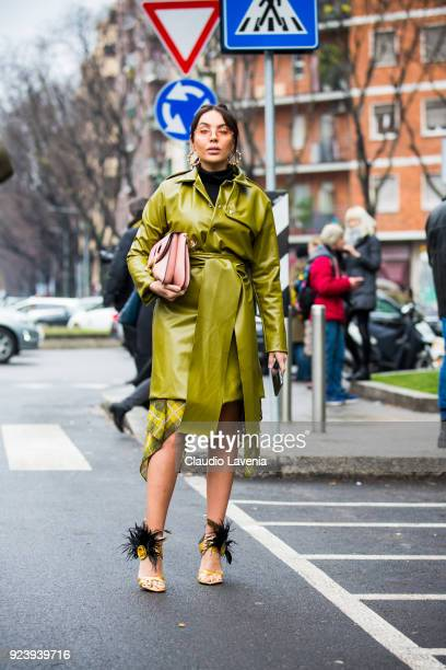 Guest wearing green trench and a JW Anderson bag is seen outside Giorgio Armani show during Milan Fashion Week Fall/Winter 2018/19 on February 24...