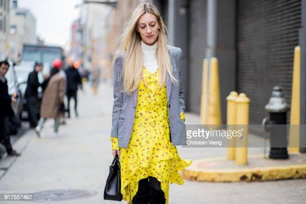 A guest wearing grey blazer yellow dress seen outside Ralph Lauren on February 12 2018 in New York City