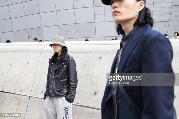 Guest wearing grey bucket hat leather rider jacket and track pants is seen at the Hera Seoul Fashion Week 2019 F/W at Dongdaemun Design Plaza at...