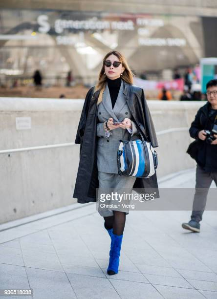 A guest wearing grey checked blazer jacket grey skirt tights Balenciaga leather coat Balenciaga bag blue ankle boots is seen at the Hera Seoul...