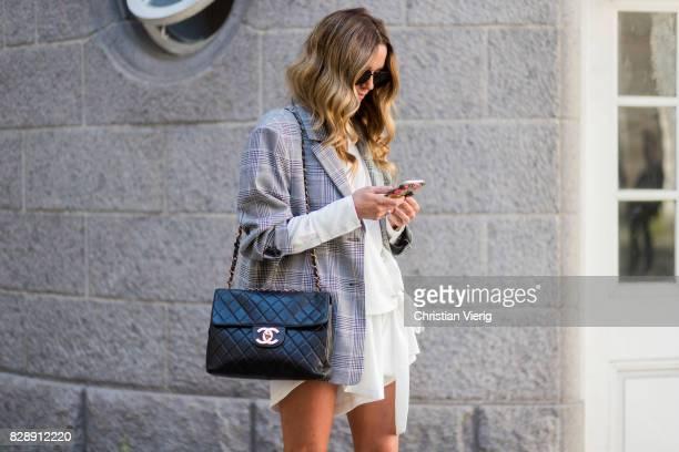 A guest wearing grey plaid blazer black Chanel bag white dress outside Holzweiler on August 09 2017 in Copenhagen Denmark