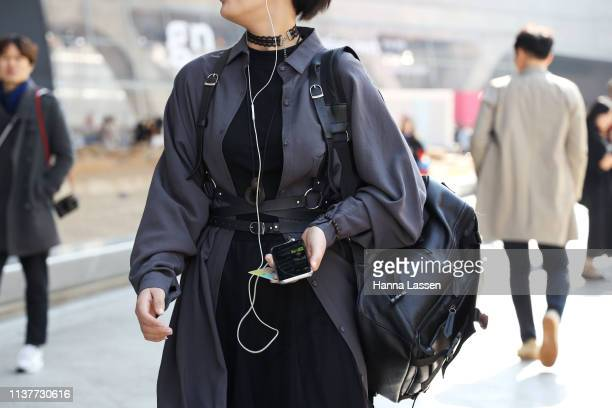 Guest wearing grey shirt jacket black dress and black leather harness is seen at the Hera Seoul Fashion Week 2019 F/W at Dongdaemun Design Plaza at...