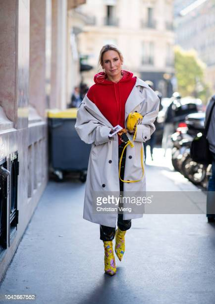 A guest wearing grey trench coat red hoody yellow ankle boots is seen outside Redemption during Paris Fashion Week Womenswear Spring/Summer 2019 on...