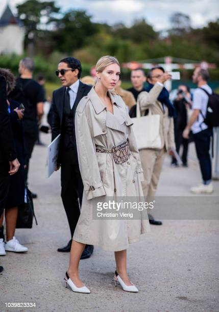 A guest wearing grey trench coat seen outside Dior during Paris Fashion Week Womenswear Spring/Summer 2019 on September 24 2018 in Paris France