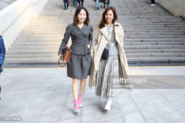 Guest wearing grey twopiece pink socks with Louis Vuitton bag and a guest wearing trench coat floral printed maxi dress white leather ankle boots and...