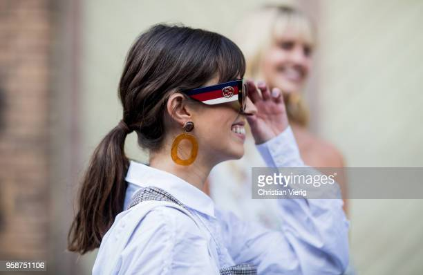 A guest wearing Gucci sunglasses earrings white button shirt grey plaid dress during MercedesBenz Fashion Week Resort 19 Collections at Carriageworks...