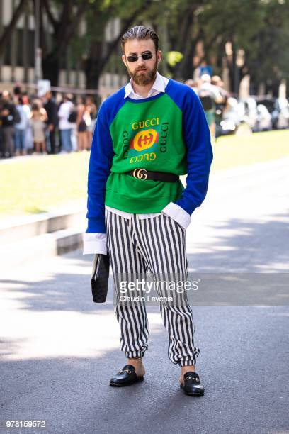 A guest wearing Gucci sweater striped pants and Gucci belt is seen in the streets of Milan after the Giorgio Armani show during Milan Men's Fashion...