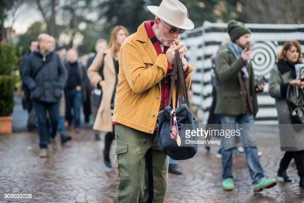 A guest wearing hat mustard jacket green pants bag is seen during the 93 Pitti Immagine Uomo at Fortezza Da Basso on January 9 2018 in Florence Italy