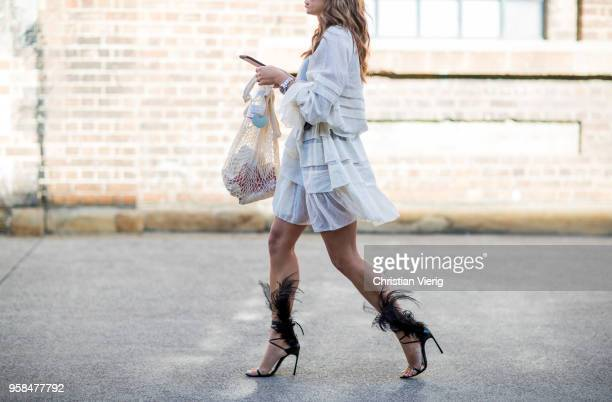 A guest wearing high heels with feather white dress during MercedesBenz Fashion Week Resort 19 Collections at Carriageworks on May 14 2018 in Sydney...